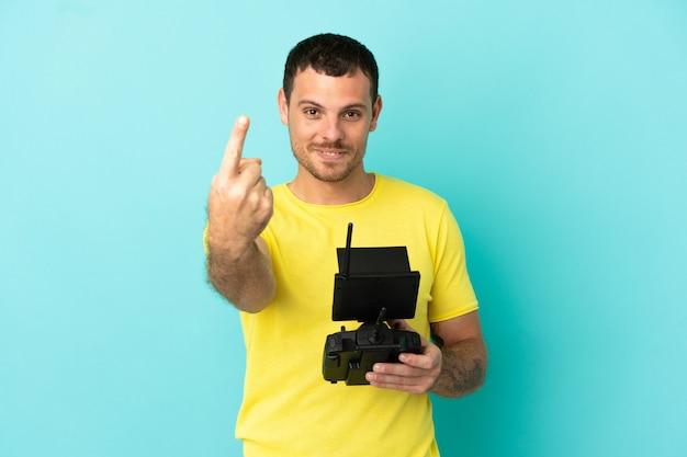 Бразильский мужчина держит пульт дистанционного управления дроном на изолированном синем фоне, делая приближающийся жест