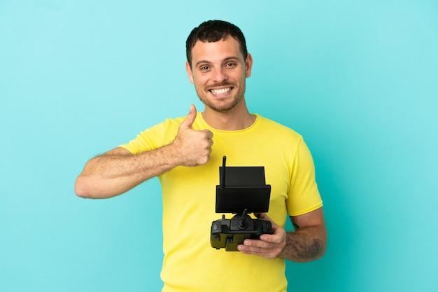 親指を立てるジェスチャーを与える孤立した青い背景の上にドローンのリモコンを保持しているブラジル人男性