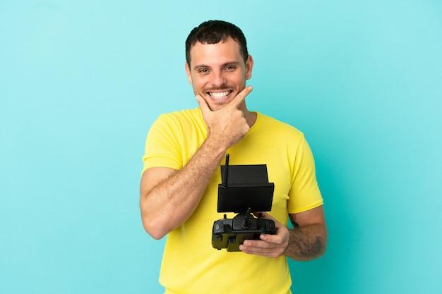 Бразильский мужчина, держащий пульт дистанционного управления дроном на синем фоне, счастлив и улыбается