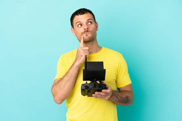 Бразильский мужчина, держащий пульт дистанционного управления дроном на изолированном синем фоне, сомневается, глядя вверх