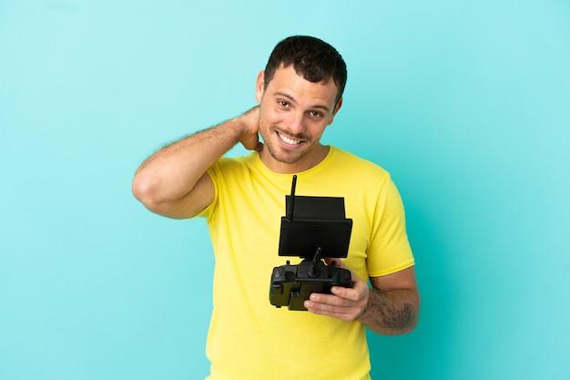 Бразильский мужчина, держащий пульт дистанционного управления дроном на синем фоне, смеется
