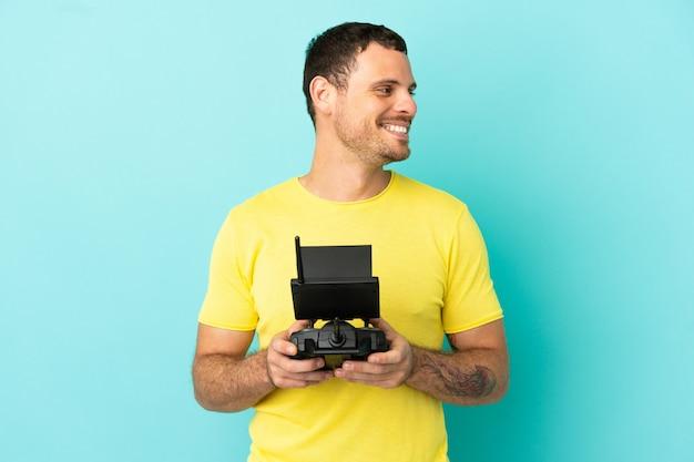 Бразильский мужчина держит пульт дистанционного управления дроном на изолированном синем фоне, глядя в сторону