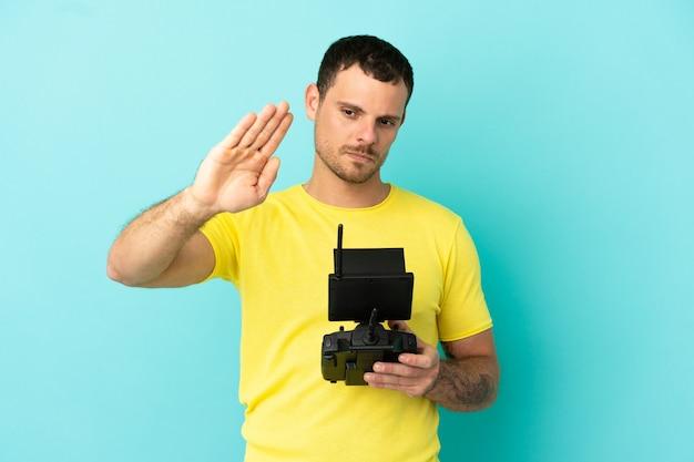 Бразильский мужчина держит пульт дистанционного управления дроном на изолированном синем фоне, делая жест стоп и разочарованный