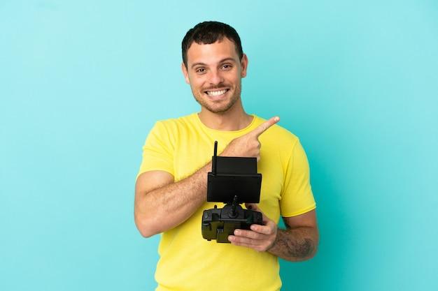 Бразильский мужчина держит пульт дистанционного управления дроном на синем фоне, указывая в сторону, чтобы представить продукт