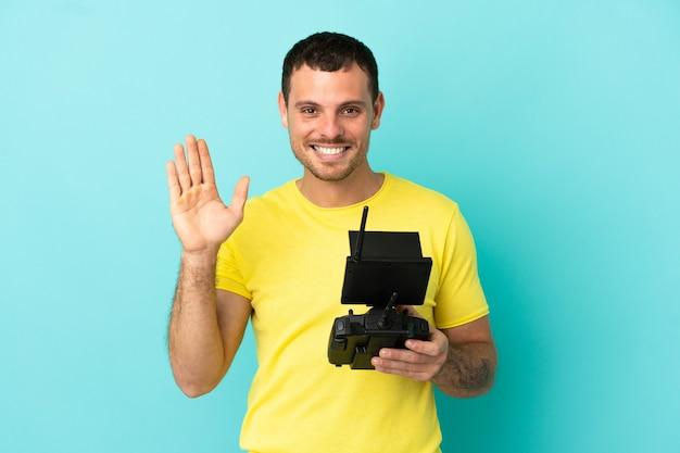 Бразильский мужчина держит пульт дистанционного управления дроном на изолированном синем фоне, салютуя рукой со счастливым выражением лица