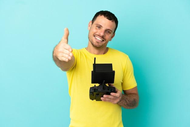 Бразильский мужчина держит пульт дистанционного управления дроном на изолированном синем фоне, пожимая руку для заключения хорошей сделки