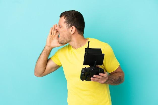 Бразильский мужчина держит пульт дистанционного управления дроном на синем фоне и кричит с широко открытым ртом