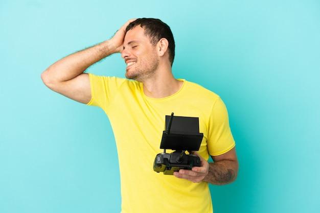 Бразильский мужчина держит пульт дистанционного управления дроном на синем фоне, много улыбаясь