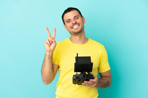 Бразильский мужчина, держащий пульт дистанционного управления дроном на синем фоне, улыбается и показывает знак победы