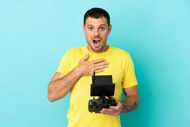 Бразильский мужчина, держащий пульт дистанционного управления дроном на изолированном синем фоне, удивлен и шокирован, глядя направо