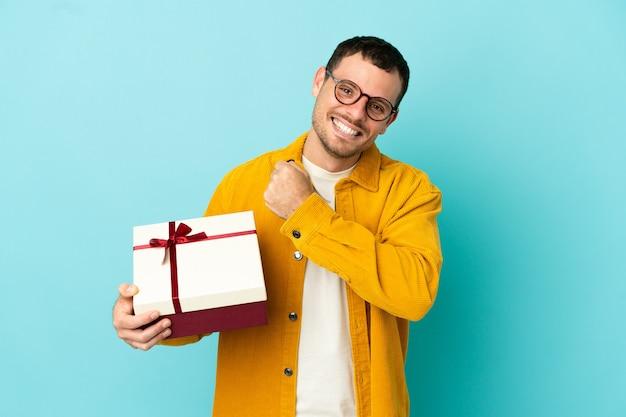 Бразильский мужчина держит подарок на синем фоне, празднует победу