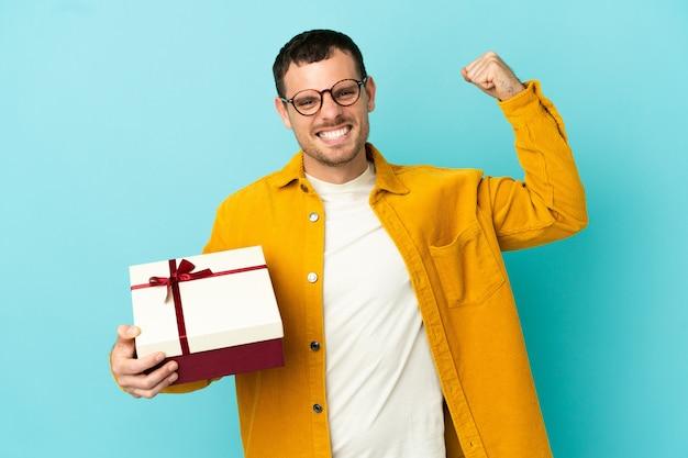 Бразильский мужчина держит подарок на изолированном синем фоне, делая сильный жест