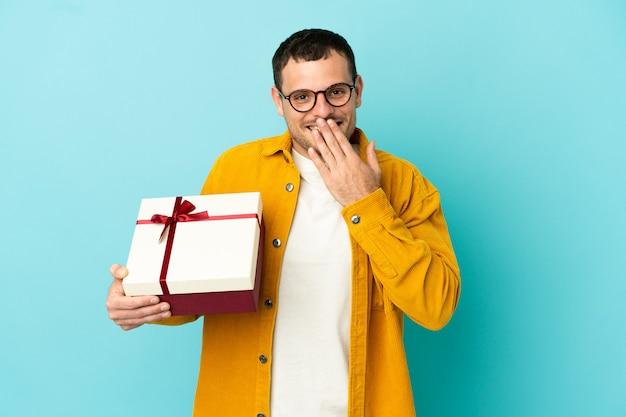 Бразильский мужчина держит подарок на синем фоне, счастливый и улыбающийся, прикрывая рот рукой