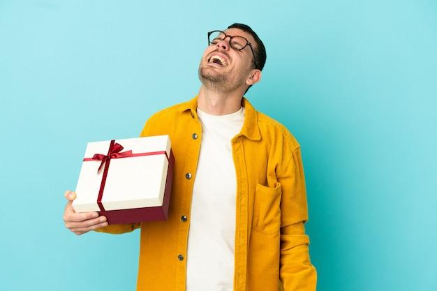 Бразильский мужчина держит подарок на синем фоне, смеясь