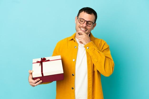 Бразильский мужчина держит подарок на синем фоне, глядя в сторону и улыбается