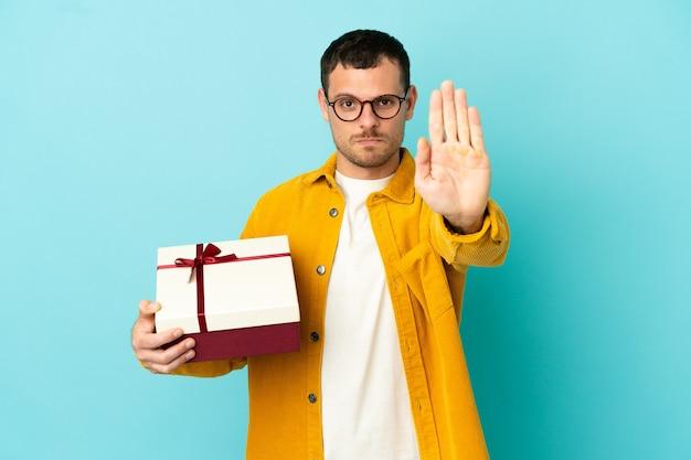 Бразильский мужчина держит подарок на синем фоне, делая стоп-жест