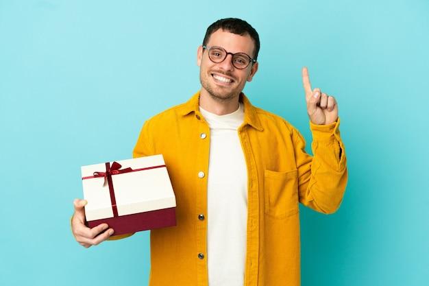 Бразильский мужчина держит подарок на синем фоне, указывая на отличную идею
