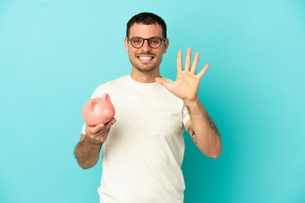 Бразильский мужчина держит копилку на синем фоне, считая пять пальцами
