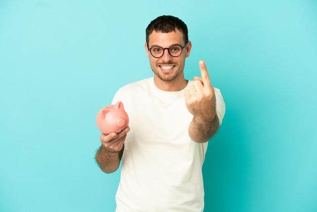 Бразильский мужчина, держащий копилку на синем фоне, делает приближающийся жест
