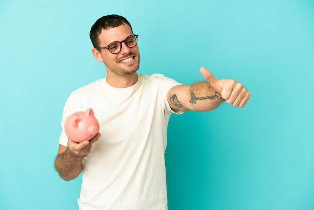 親指を立てるジェスチャーを与える孤立した青い背景の上に貯金箱を保持しているブラジル人男性