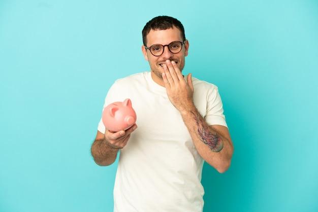 Бразильский мужчина держит копилку на синем фоне, счастливый и улыбается, прикрывая рот рукой
