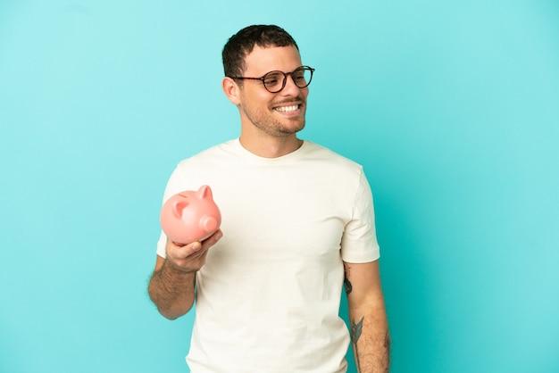 Бразильский мужчина держит копилку на синем фоне, глядя в сторону и улыбается