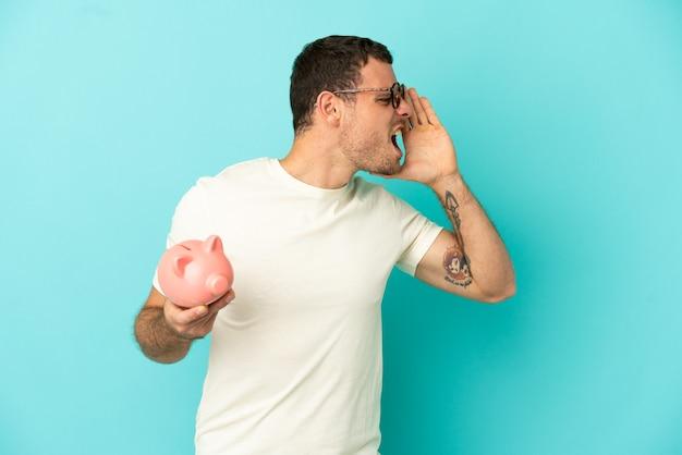 Бразильский мужчина держит копилку на синем фоне и кричит с широко открытым ртом