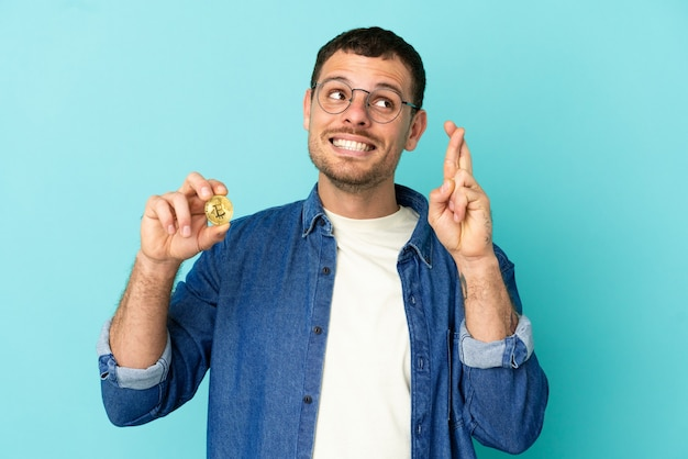 Brazilian man holding a bitcoin over isolated blue background with fingers crossing and wishing the best