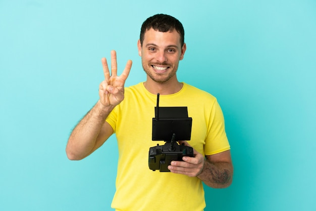 Brazilian man holding a drone remote control over isolated blue background happy and counting three with fingers