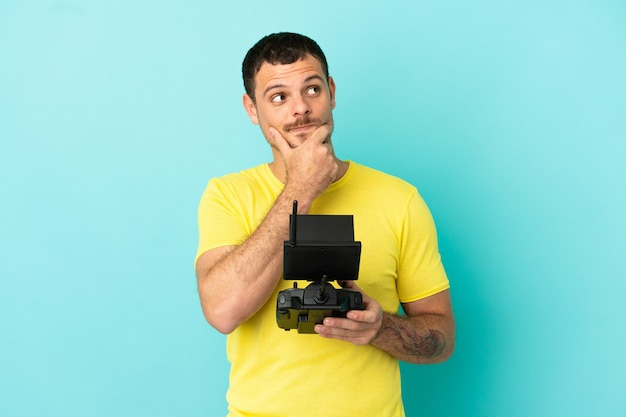Brazilian man holding a drone remote control over isolated blue background having doubts