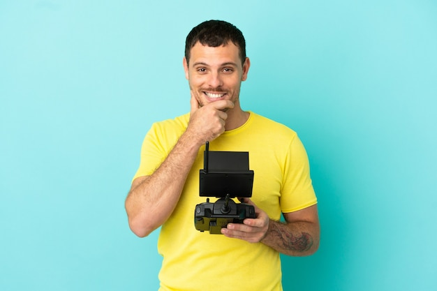 Brazilian man holding a drone remote control over isolated blue background thinking