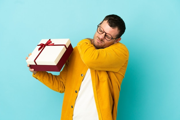 Brazilian man holding a gift over isolated blue background suffering from pain in shoulder for having made an effort