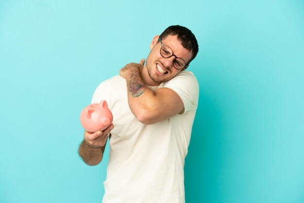 Brazilian man holding a piggybank over isolated blue background suffering from pain in shoulder for having made an effort