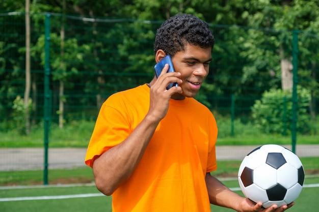 Бразильский мужчина держит футбольный мяч и использует смартфон на спортивной площадке
