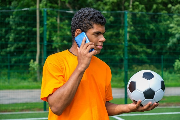 Brazilian man holding soccer ball and use smartphone on sports court