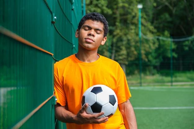울타리에 서 있는 동안 축구 공을 들고 브라질 남자