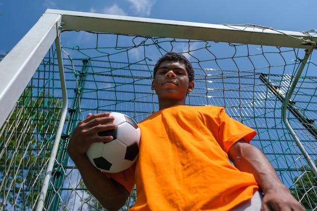축구 골대에 서 있는 동안 축구공을 들고 있는 브라질 남자