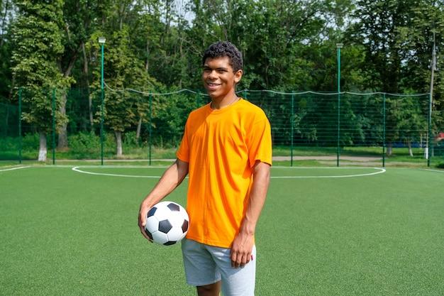 Бразильский мужчина держит футбольный мяч, стоя на спортивной площадке