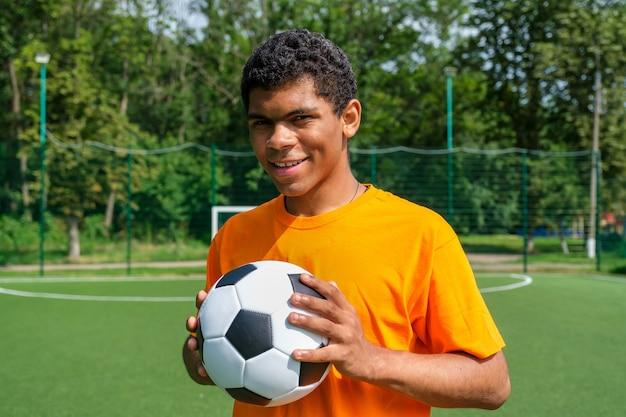 스포츠 코트에 서 있는 동안 축구 공을 들고 브라질 남자