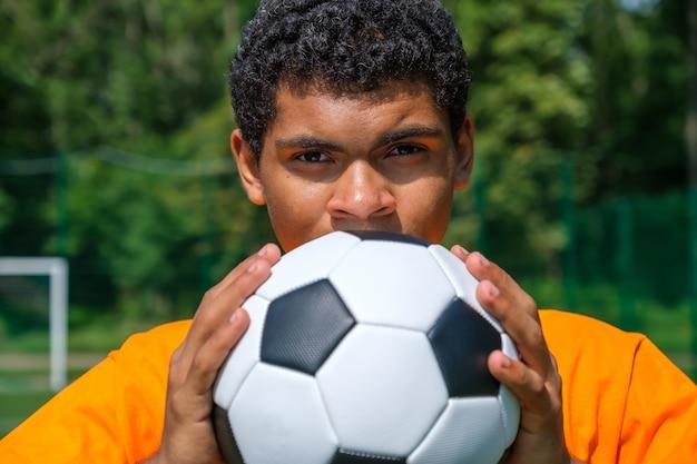 스포츠 코트에 서 있는 동안 브라질 남자가 축구공을 가까이서 보유하고 있습니다.