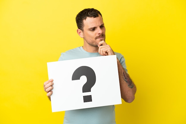 Brazilian man over isolated purple background holding a placard with question mark symbol and thinking
