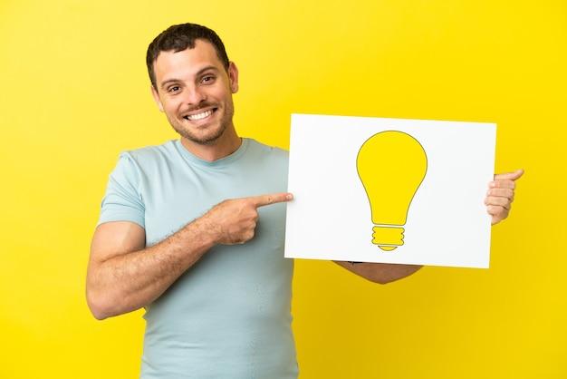 Бразильский мужчина на изолированном фиолетовом фоне держит плакат со значком лампочки и указывает на него