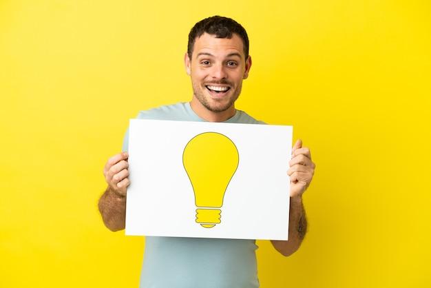 Бразильский мужчина на изолированном фиолетовом фоне держит плакат со значком лампочки со счастливым выражением лица