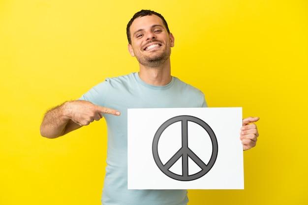 Бразильский мужчина на изолированном фиолетовом фоне держит плакат с символом мира и указывает на него