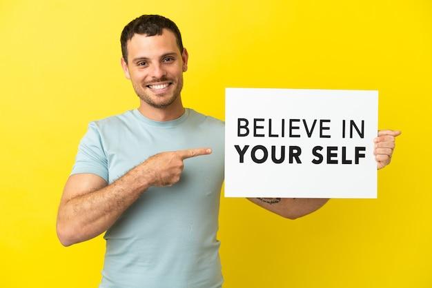 격리 된 보라색 배경 위에 브라질 남자 텍스트와 현수막을 들고 자신을 믿고 그것을 가리키는