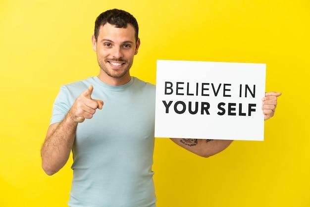 격리 된 보라색 배경 위에 브라질 남자 텍스트와 현수막을 들고 자신을 믿고 앞을 가리키는