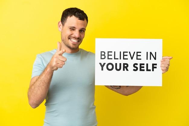 고립된 보라색 배경 위에 있는 브라질 남자는 자신을 믿으라는 문구가 적힌 플래카드를 들고 앞을 가리키고 있습니다.