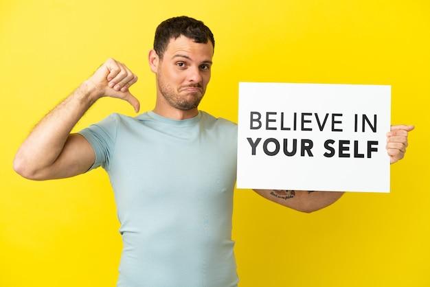 고립된 보라색 배경 위에 있는 브라질 남자는 자랑스러운 제스처로 자신을 믿으라는 문구가 적힌 플래카드를 들고