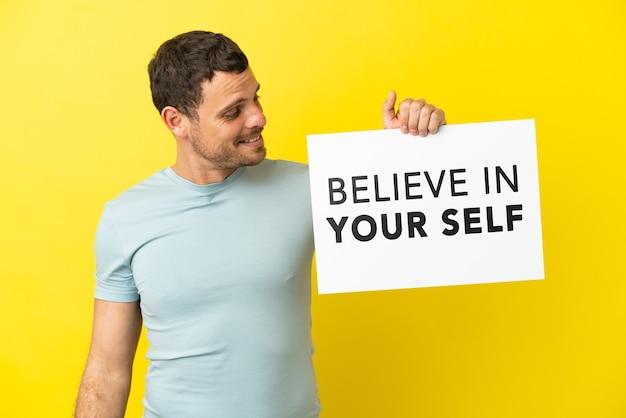 자신을 믿으라는 문구가 적힌 플래카드를 들고 고립된 보라색 배경 위에 있는 브라질 남자