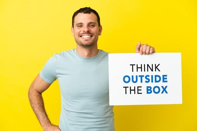 고립된 보라색 배경 위에 있는 브라질 남자는 행복한 표정으로 상자 밖에서 생각하는 현수막을 들고 있다